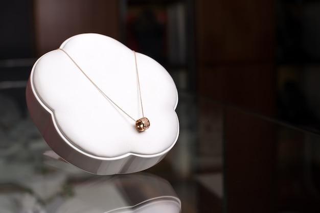 Красивое золотое колье с бриллиантами на белой подставке. свободное место для текста. роскошные украшения, женские аксессуары в витрине магазина.