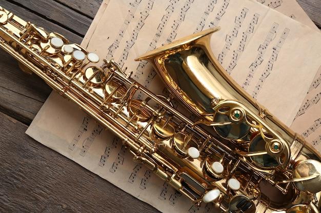 Красивый золотой саксофон с музыкальными нотами на деревянных, крупным планом