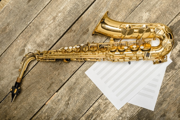 Beautiful golden saxophone on wooden background