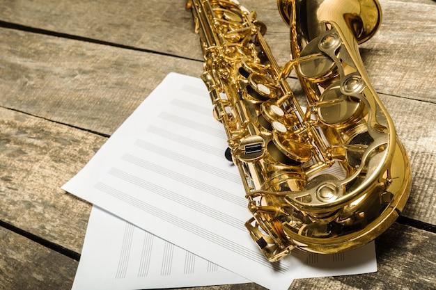 Beautiful golden saxophone on wooden surface