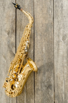 Beautiful golden saxophone on wooden