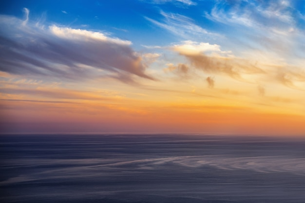 일몰 시간에 바다 위의 아름다운 황금빛 하늘