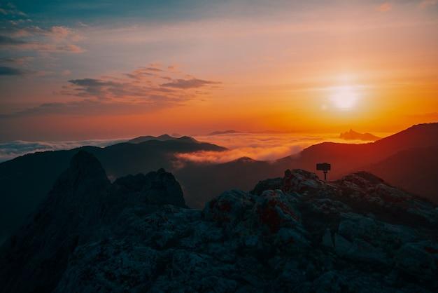 霧の中の山々の美しい黄金の夕日