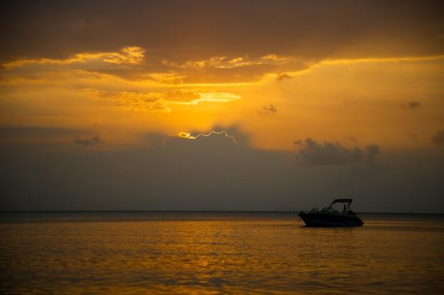 海の美しい黄金の夕日。夕方の太陽の光の中でスピードボート。