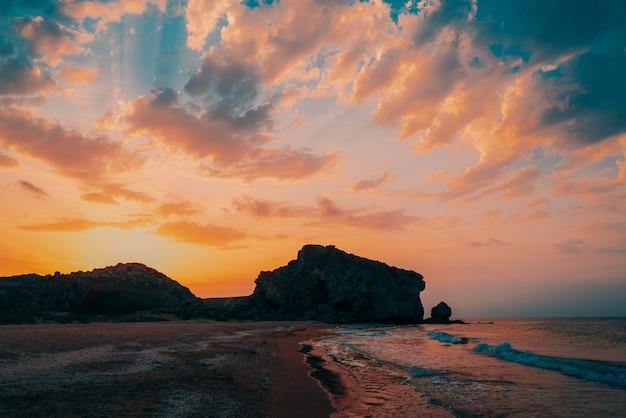 Красивый золотой закат на песчаном пляже на берегу моря