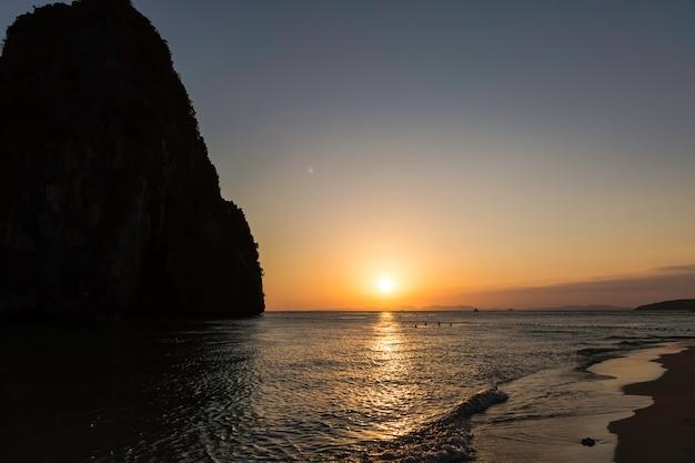 Красивый золотой закат на пляже пхра нанг в краби в таиланде песчаный пляж и люди купаются