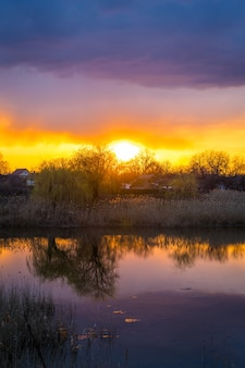 Beautiful golden sunset with reflection of clouds in the lake