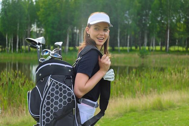 ゴルフバッグを持って笑顔の美しいゴルフ女性プレーヤー。