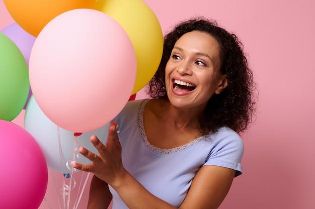 テキストのためのスペースとピンク色の背景に対してポーズをとって膨らんだ明るい風船を通して覗く美しい歯を見せる笑顔でかわいい笑顔の美しいゴージャスな魅力的な見事な陽気な女性