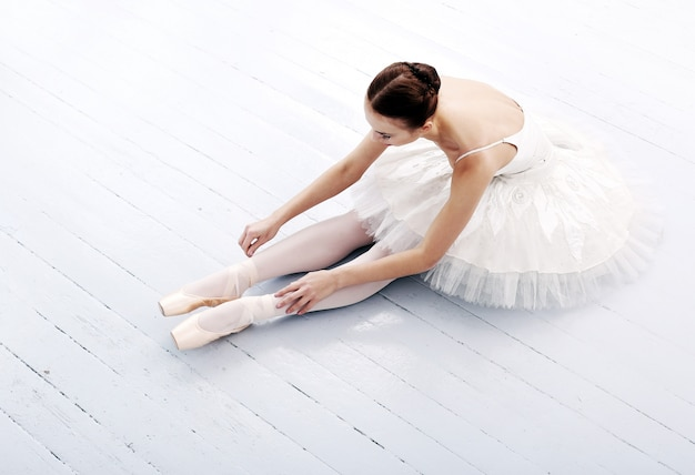 Beautiful and gorgeous ballerina sitting on the floor