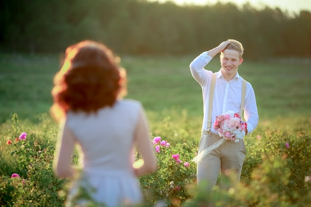 Beautiful gorgeous bride and stylish handsome groom, rustic couple in a rose field