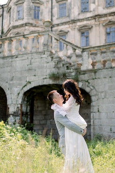 Beautiful gorgeous chinese bride and groom walking in sunny day and kissing.