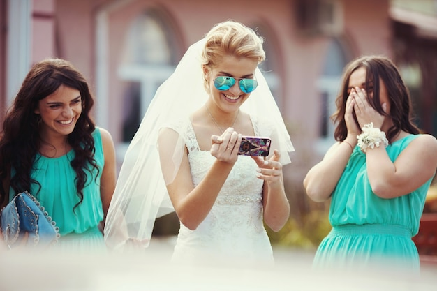 Beautiful gorgeous happy blonde bride with bridesmaids on the street on the background restaurant