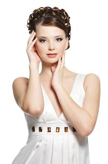 短い巻き毛のヘアスタイルを持つ美しいゴージャスな女性。白い壁に