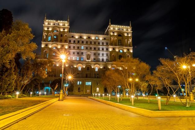 Красивый дом правительства баку, расположенный посреди небольшого сада ночью