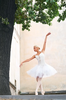 Beautiful graceful ballerina dancing on the streets of an old ci