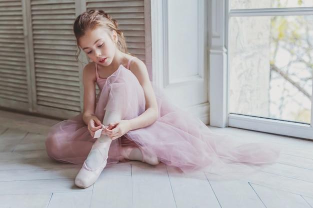 ピンクのチュチュスカートの美しい優雅なバレリーナは、大きな窓の近くにトウシューズを履きます