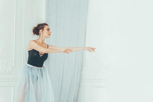 하얀 빛 홀의 큰 거울 근처에 파란색 투투 스커트에 아름다운 우아한 발레리나 연습 발레 위치