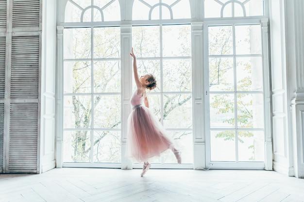 Красивые изящные балерины практикуют балетные позы в розовой юбке-пачке возле большого окна в зале с белым светом