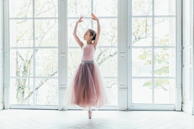 大きな窓の近くのチュチュスカートで美しい優雅なバレリーナ練習バレエの位置
