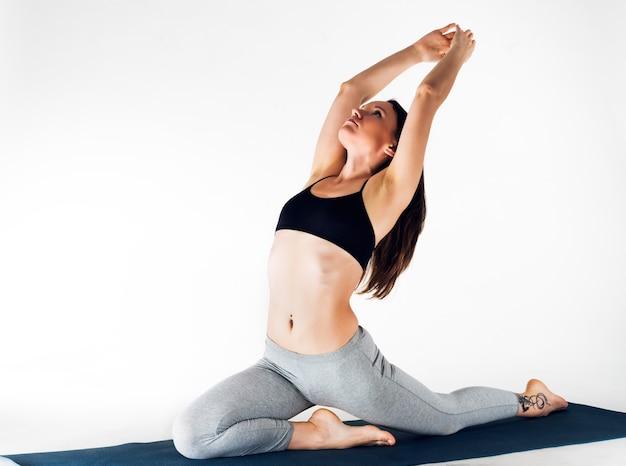 Красивая изящная молодая кавказская женщина-спортсмен делает упражнение лягушки, лежа на ковре на полу на белой стене