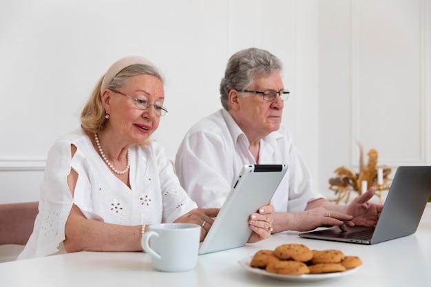 デジタルデバイスの使い方を学ぶ美しい祖父母のカップル 無料写真