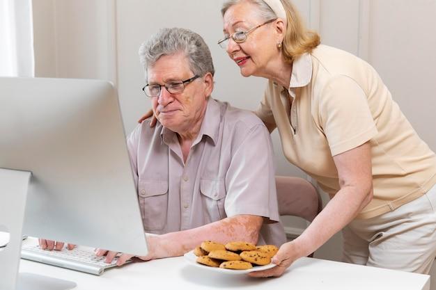 デジタルデバイスの使い方を学ぶ美しい祖父母のカップル