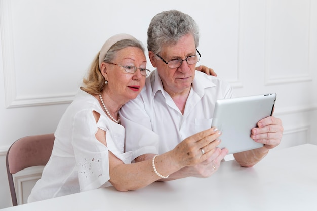 Beautiful grandparents couple learning to use digital device