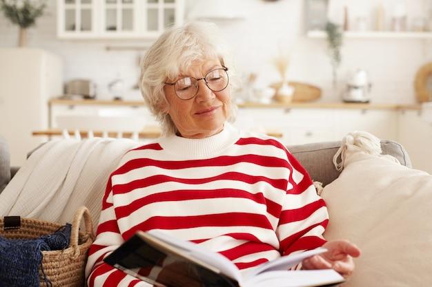 책을 소파에 앉아 소설을 읽고 즐기는 세련 된 라운드 안경에 아름 다운 회색 머리 수석 유럽 여자. 흥미 진진한 교과서를 통해보고 집에서 쉬고있는 매력적인 할머니