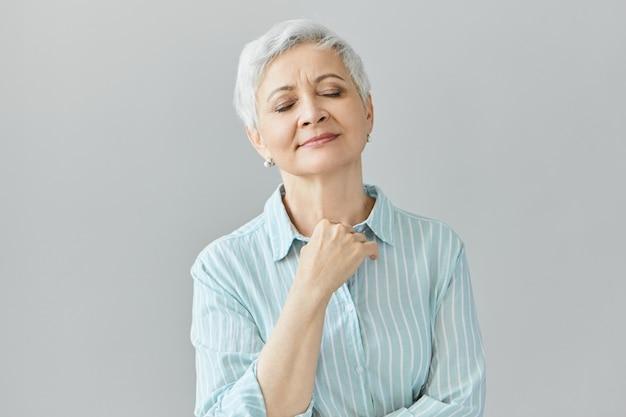 青い縞模様のシャツを着た美しい白髪の女性年金受給者は目を閉じて平和に笑い、良いクラシック音楽を楽しみ、懐かしい表情を持ち、胸を抱えています