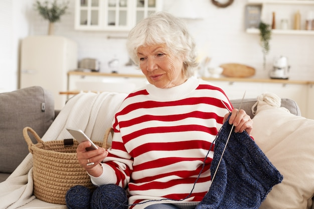 Beautiful gray haired woman on retirement spending rainy day at home sitting on couch and knitting, holding mobile, typing text message. elegant grandmother messaging grandson online using cell phone
