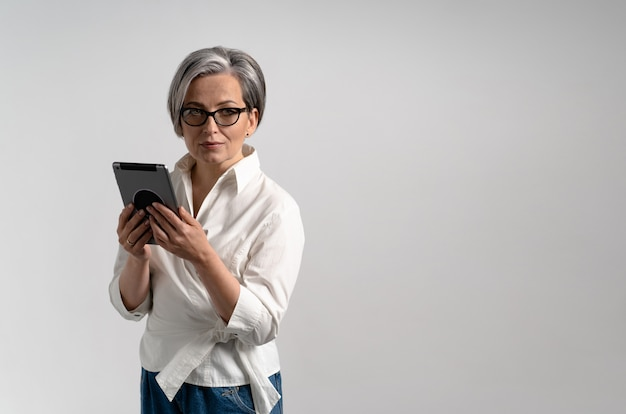 Beautiful graying businesswoman holds digital tablet while posing