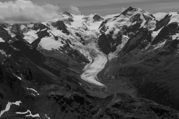 Beautiful grayscale shot of snowy rocky mountains