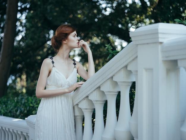 公園の豪華な神話の王女の白いドレスを着た美しいギリシャの女性