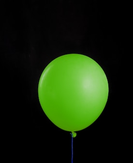 Beautiful green balloon on black isolated background. layout gift concept