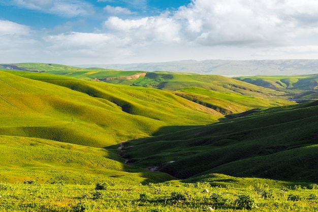 Beautiful green hills with clouds on blue sky landscape
