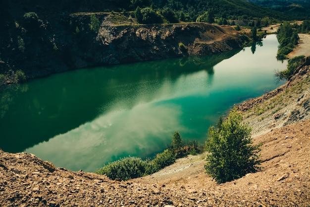 植生に囲まれた砕石の岩の多い海岸と細長い形の美しい緑の湖。鉱物の抽出のための浸水した深い採石場。