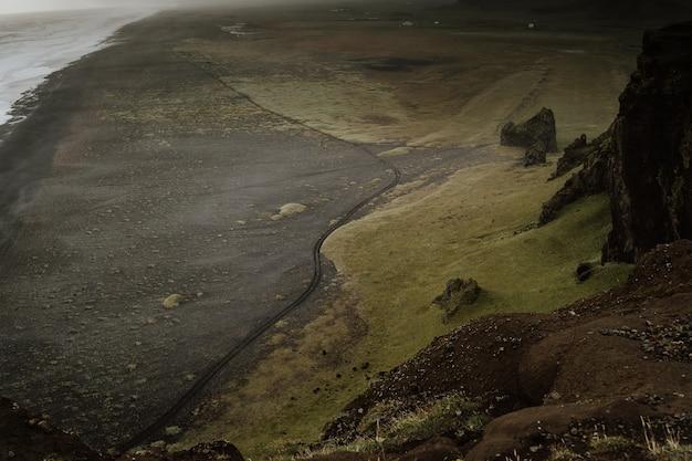 霧の日に海沿いの丘のある美しい緑豊かな土地