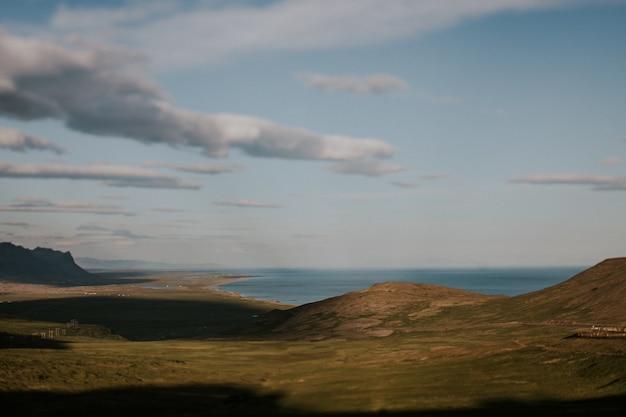 曇り空の下の丘の美しい緑の風景