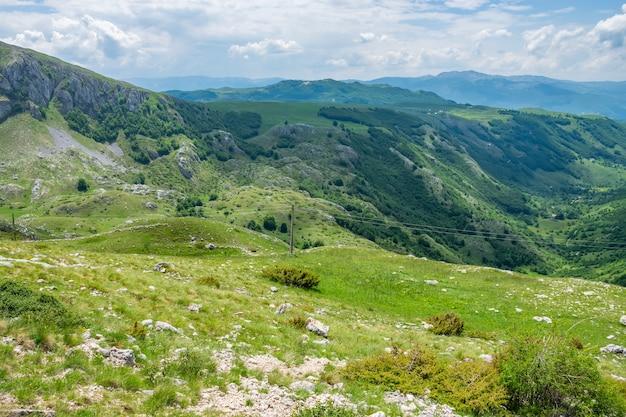 絵のように美しい山々に広がる美しい緑の牧草地。