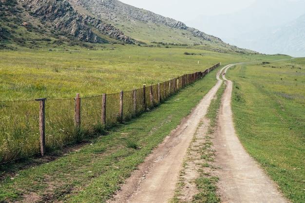 柵に沿った長い未舗装の道路と霧の中の大きな山々のある美しい緑の山の風景。岩と大きな山々の間の未舗装の道路と大気の霧の山の風景。田舎の長さの道