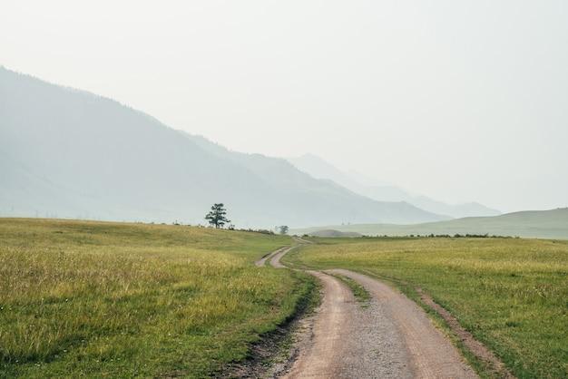 長い未舗装の道路と霧の中の大きな山々のある美しい緑の山の風景。丘の間に長い道がある大気の霧の山の風景。大きな山の未舗装の道路の近くの木への風光明媚な景色。
