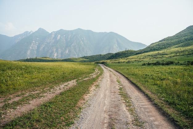 長い未舗装の道路と霧の森のある大きな山々のある美しい緑の山の風景。木々のある丘の間の未舗装の道路と大気の霧の山の風景。大きな山の長さの道。