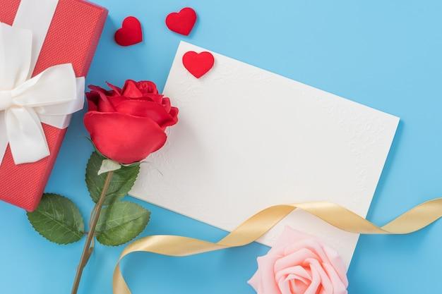 美しい挨拶の招待カード、母の日、バレンタインデー、記念日、誕生日の青い色の背景に分離、コピースペース、上面図、フラットレイの概念