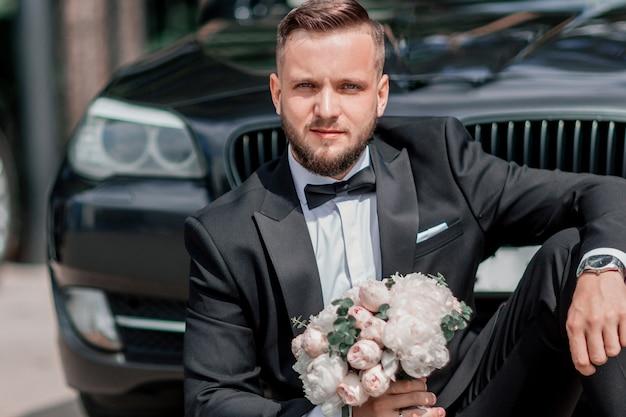 Beautiful groom sitting near the wedding car.