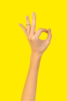 노란색 괜찮아 제스처와 아름 다운 손질 된 여자 손