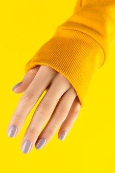 노란색에 유행 네일 디자인으로 아름 다운 손질 된 여자 손