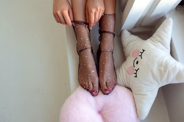 星の靴下で美しい手入れをされた女性の足。爪と清潔で柔らかく滑らかな体の皮膚に注意してください。ペディキュアとマニキュアの美容院。