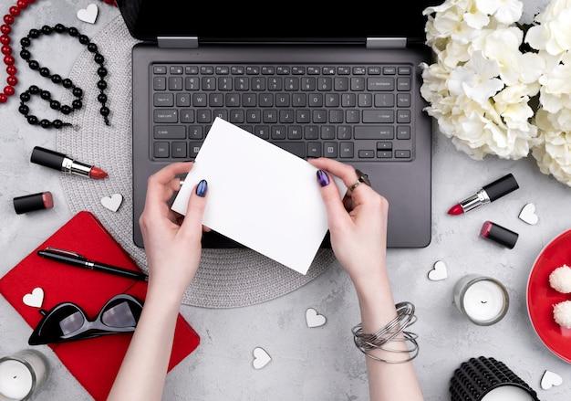 ホームオフィスのテーブルにビジネスグリーティングカードを保持している手入れの行き届いた美しい女性の手