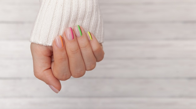 Beautiful groomed woman's hands with colored nails